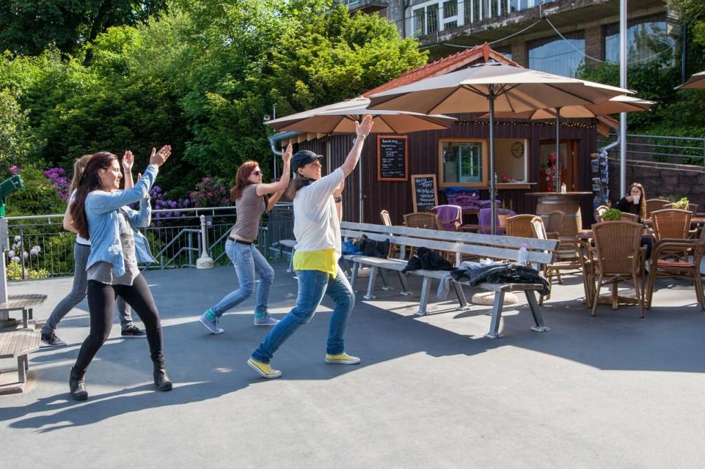 Vier Tänzerinnen tanzen auf einer Freifläche vor dem Kiosk mit Außenbestuhlung