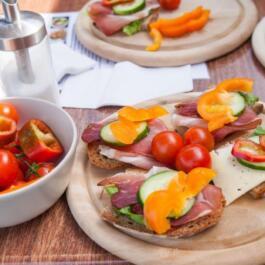 Belegte Brote mit Schinken und Käse auf einem Holzbrett. Dazu Cherrytomaten und Paprika