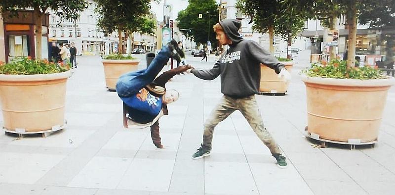 Zwei Tänzer zwischen Blumenkübeln auf dem Bismarckplatz