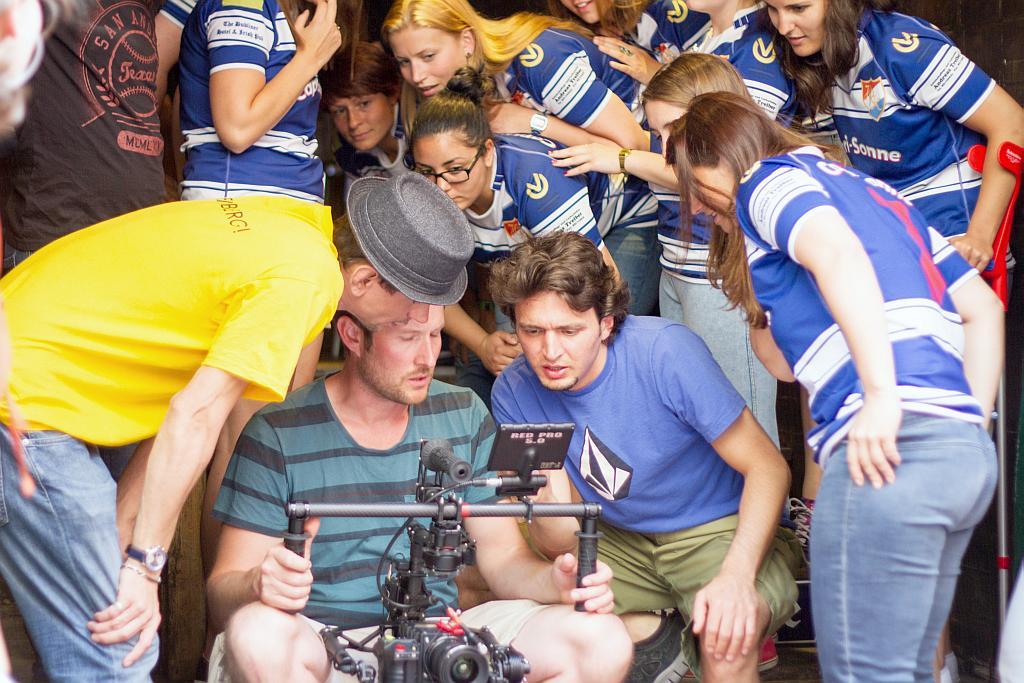 Filmteam und Rugbyteam steht gespannt um das Display der Kamera herum.