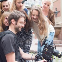 Tänzerinnen und Videoteam stehen um den Monitor herum