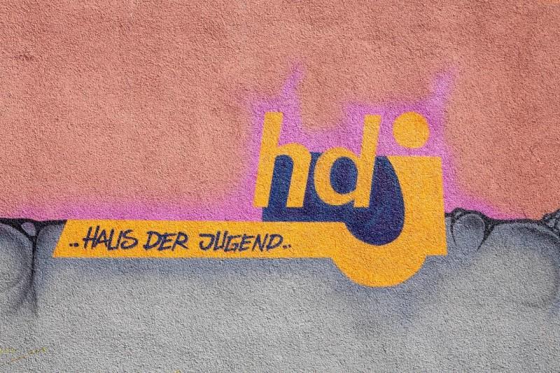 Wand, an die in warmen Farben das Logo hdj gemalt ist.