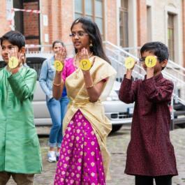 Drei minderjährige bunt gekleidete indische Tänzer halten runde Schilder mit mit den Buchstaben H A P P Y hoch