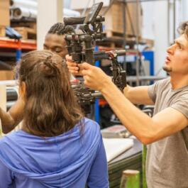 Tänzer blicken auf eine Zeitung Kameramann von hinten